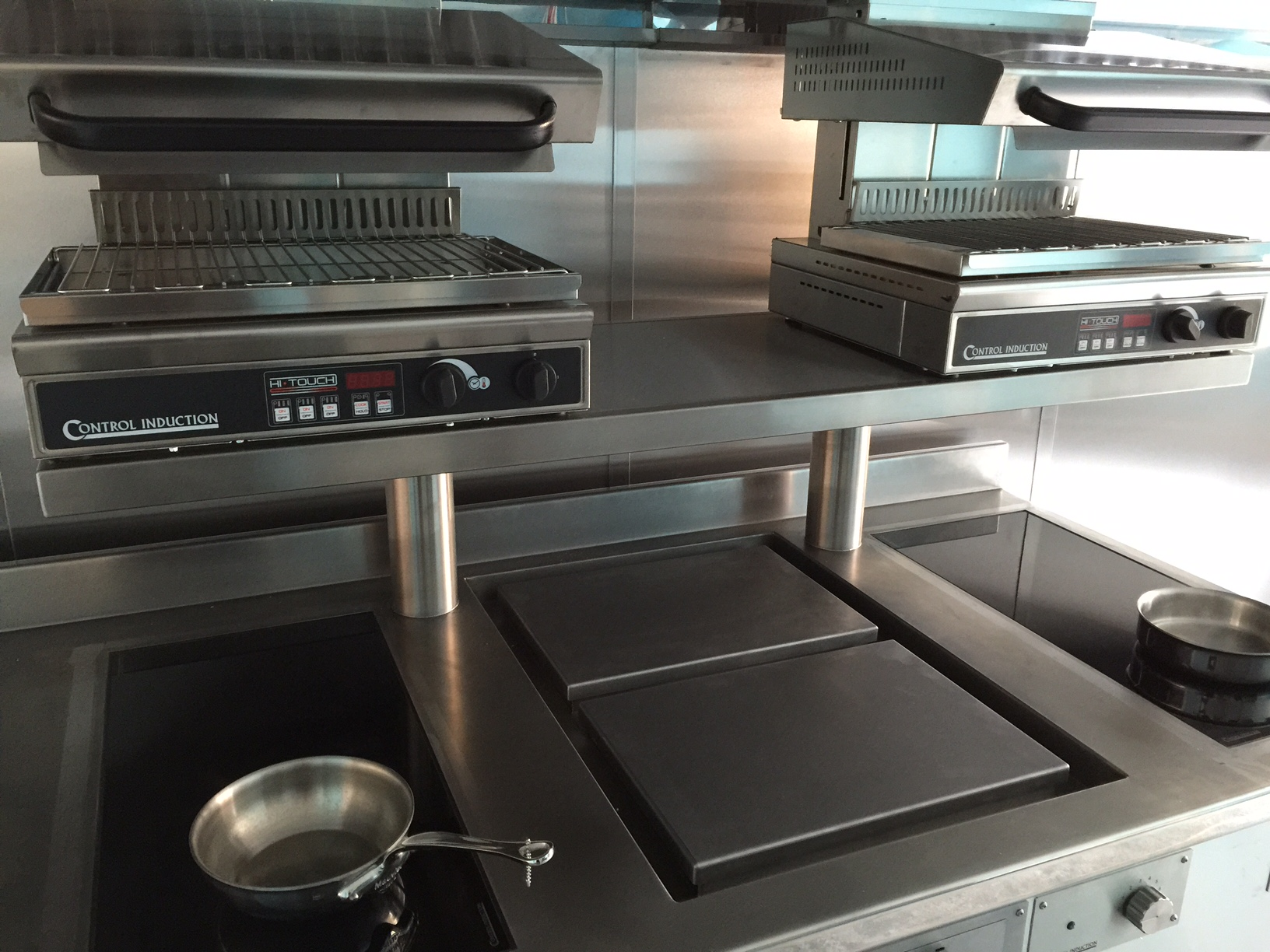 Induction cooking suite with salamanders over