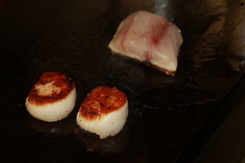 Plancha cooking scallops and fish